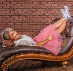 """This is a promotional photo of Erin Ramsey, host of the podcast """"You're Such a Catch."""" She is laying back on a chaise lounge with her head propped on a football as she looks over at the camera smiling."""