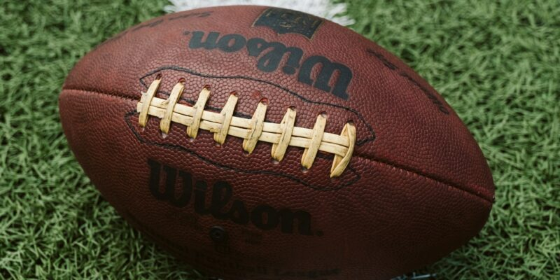 This is a photograph of a brown football sitting on a white yard line on a green football field.