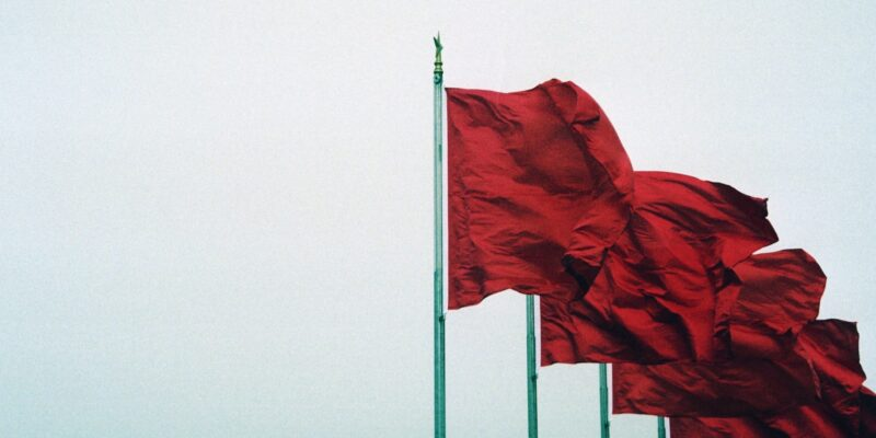 This is an outdoor photo of a group of red flags on poles.